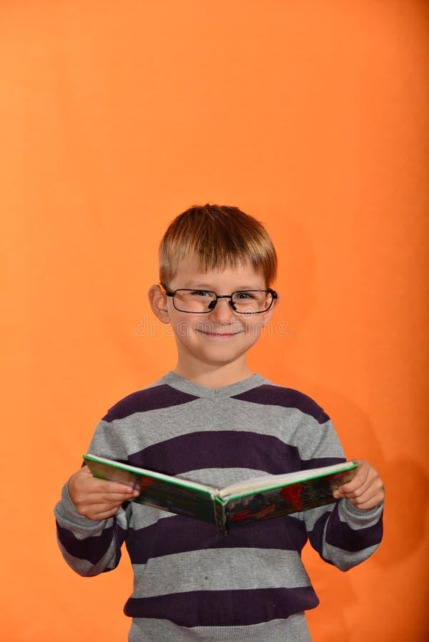 Porträt eines Jungen in den Gläsern mit einem Buch in seinen Händen, ein netter Schüler auf einem gelben Hintergrund lizenzfreie stockfotos