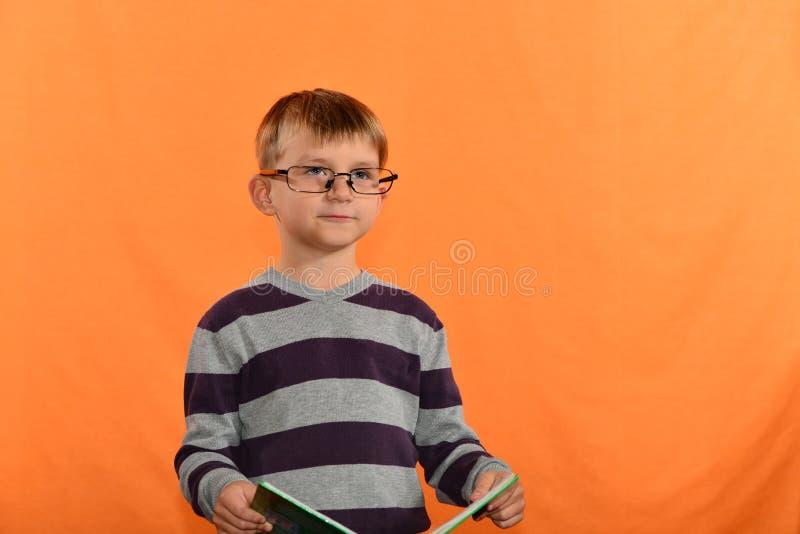 Porträt eines Jungen in den Gläsern mit einem Buch in seinen Händen, ein netter Schüler auf einem gelben Hintergrund lizenzfreie stockbilder