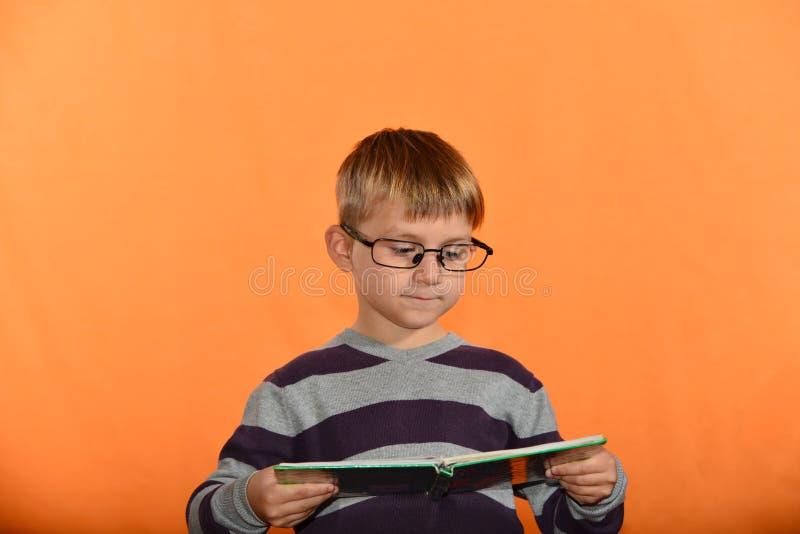 Porträt eines Jungen in den Gläsern mit einem Buch in seinen Händen, ein netter Schüler auf einem gelben Hintergrund lizenzfreie stockfotografie