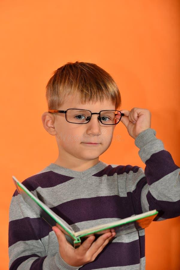 Porträt eines Jungen in den Gläsern mit einem Buch in seinen Händen, netter Schüler auf einem gelben Hintergrund richtet seine Gl lizenzfreies stockfoto