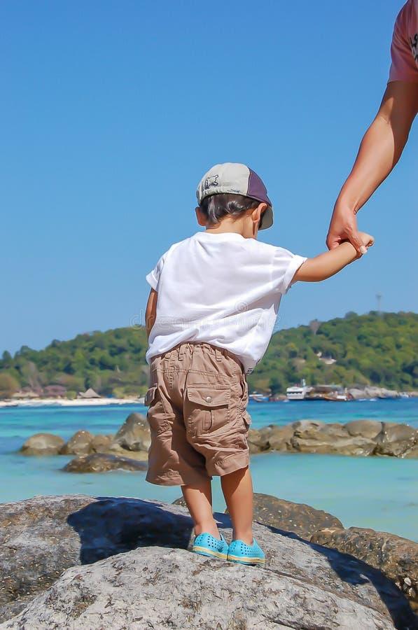 Porträt eines Jungen, der auf einem Felsen durch das Meer steht lizenzfreie stockbilder