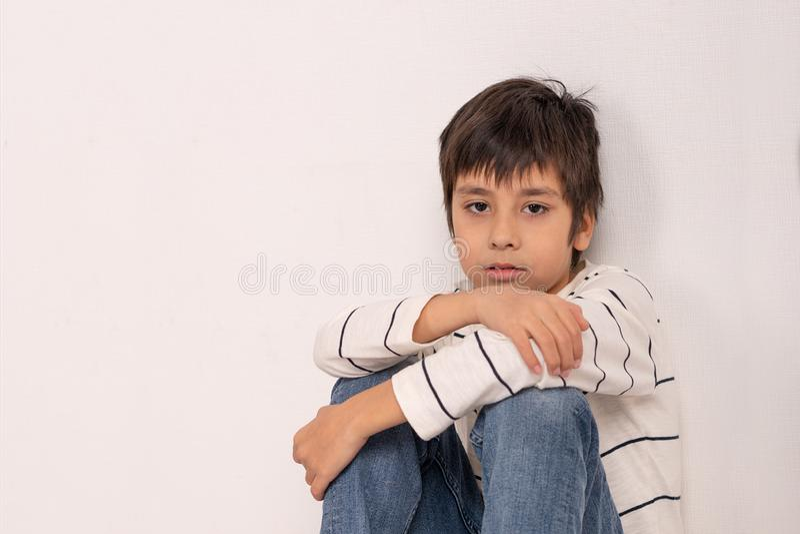 Porträt eines Jungen, der ein weißes Hemd und Jeans stationieren auf dem Boden durch die Wand trägt und denkt oder, die an etwas  lizenzfreies stockbild