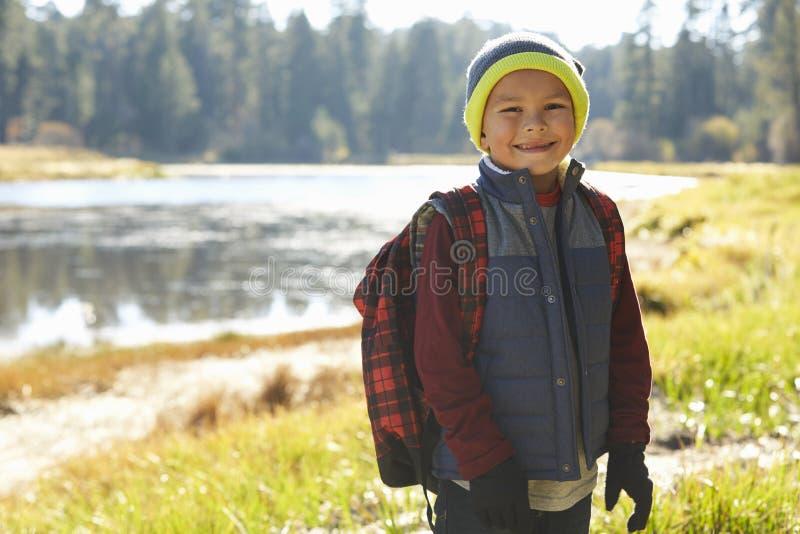 Porträt eines Jungen, der einen See auf einem Camping-Ausflug bereitsteht lizenzfreie stockfotos