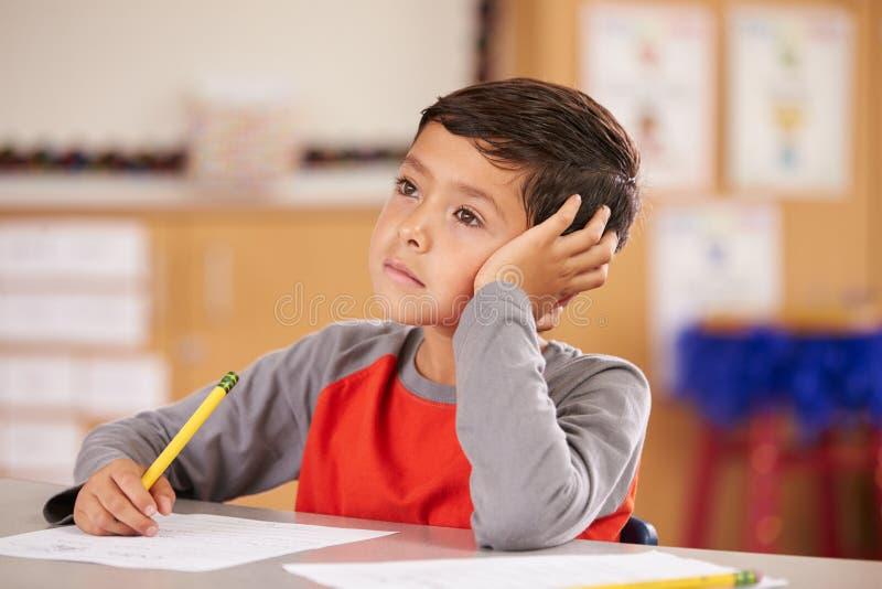 Porträt eines Jungen, der in einer grundlegenden Schulklasse träumt lizenzfreie stockbilder