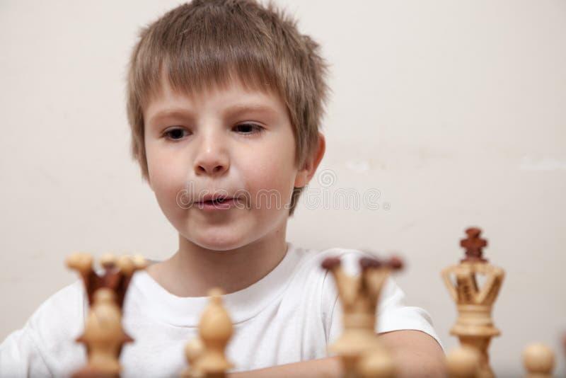 Porträt eines Jungen, der Schach spielt lizenzfreie stockbilder