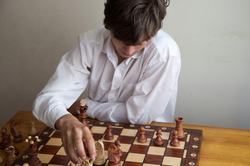 Porträt eines Jungen, der Schach spielt lizenzfreies stockfoto