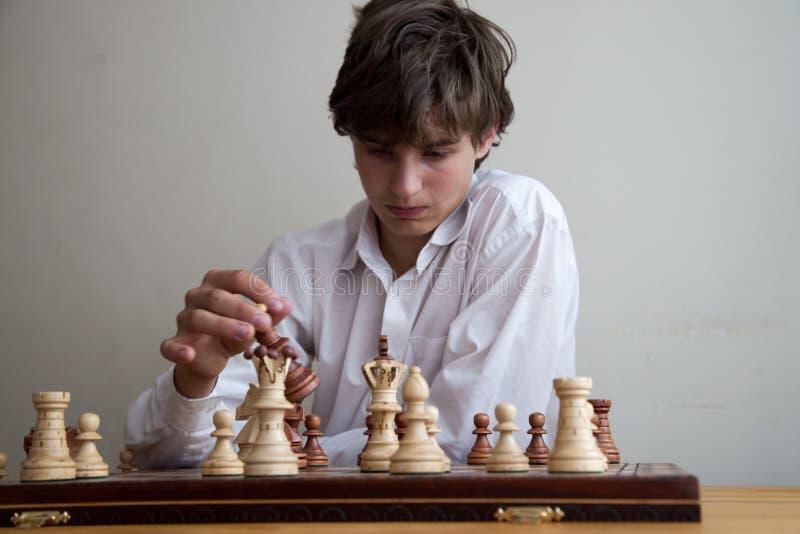 Porträt eines Jungen, der Schach spielt lizenzfreie stockfotos