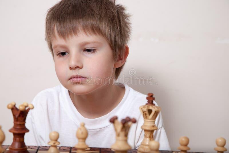 Porträt eines Jungen, der Schach spielt stockbilder