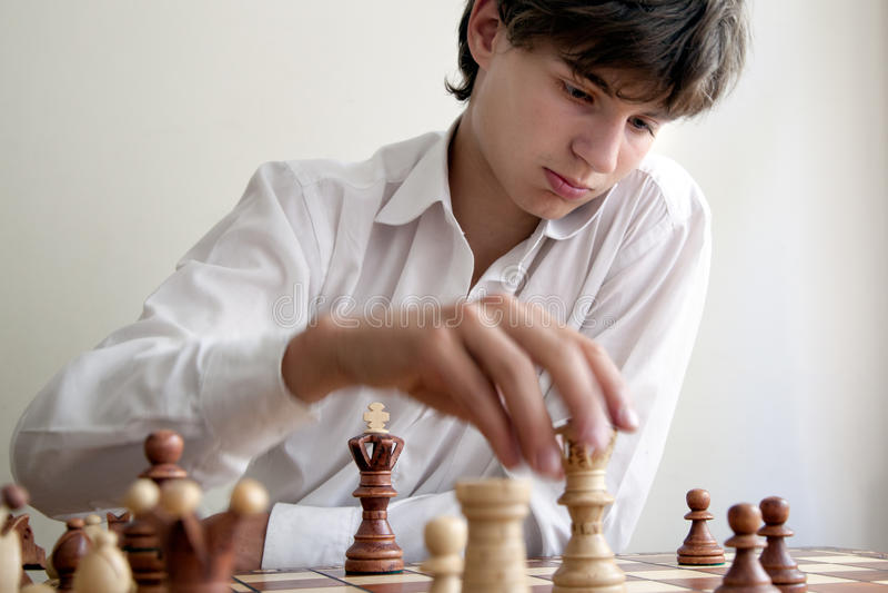 Porträt eines Jungen, der Schach spielt stockbild