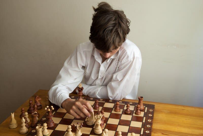 Porträt eines Jungen, der Schach spielt lizenzfreie stockfotografie