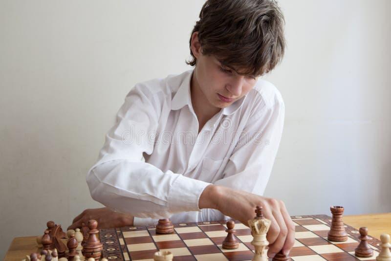 Porträt eines Jungen, der Schach spielt stockfotografie
