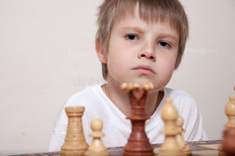 Porträt eines Jungen, der Schach spielt stockfotos
