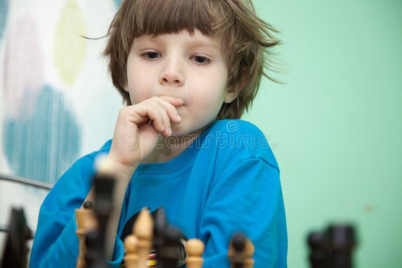Porträt eines Jungen, der Schach spielt lizenzfreies stockbild