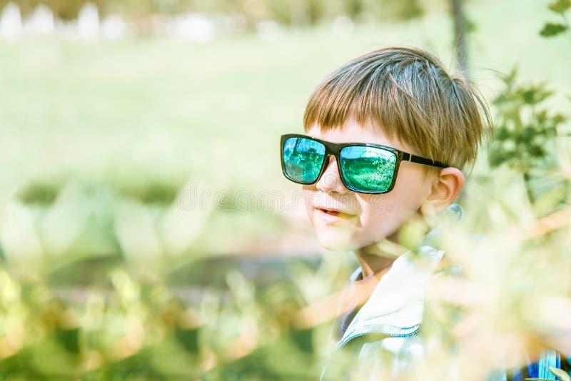 Porträt eines Jungen in der Sonnenbrille auf der Natur, auf einem grünen Hintergrund stockfoto