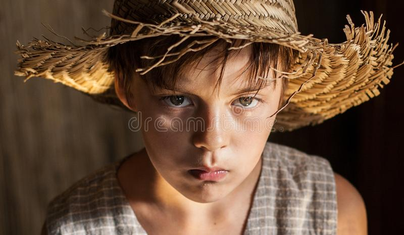 Porträt eines Jungen in einem Strohhut und in einer Weste lizenzfreie stockfotografie