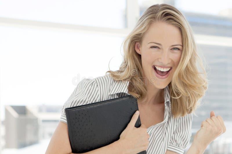 Porträt eines jungen ekstatischen Frauenholdingordners lizenzfreie stockbilder