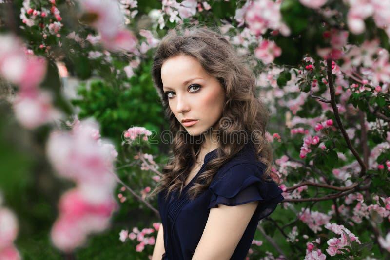 Porträt eines jungen gelockten Mädchens in einem blauen Kleid, das unter einem blühenden Apfelbaum steht stockfotografie