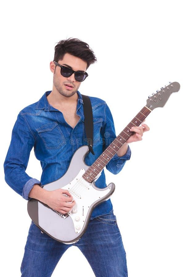 Porträt eines jungen Gitarristen, der eine E-Gitarre spielt stockbild