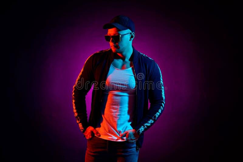 Porträt eines jungen glücklichen ernsten Mannes am Studio Männliches Modell der Haute Couture in den bunten hellen Neonlichtern,  stockbild