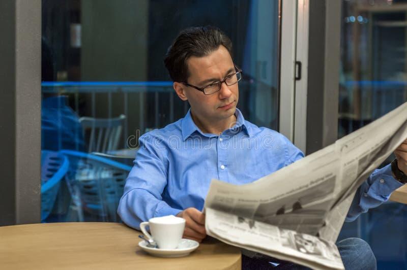 Porträt eines jungen hübschen Geschäftsmannes, der eine Zeitung an seinem Frühstück in der Kaffeestube liest lizenzfreie stockbilder