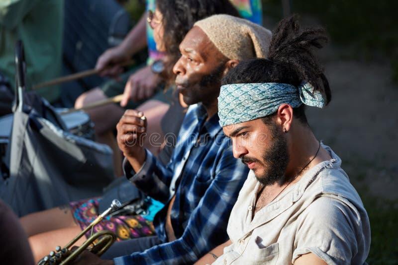 Porträt eines jungen hübschen hispanischen Latino und des männlichen Trompeters des Afroamerikaners, die neben einander sitzen stockfoto
