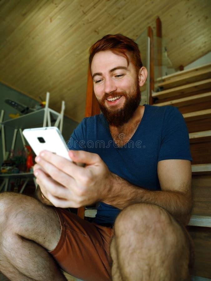 Porträt eines jungen hübschen Rothaarigemannes mit einem Bart, der sich zu Hause mit durch Handy entspannt lizenzfreie stockfotos