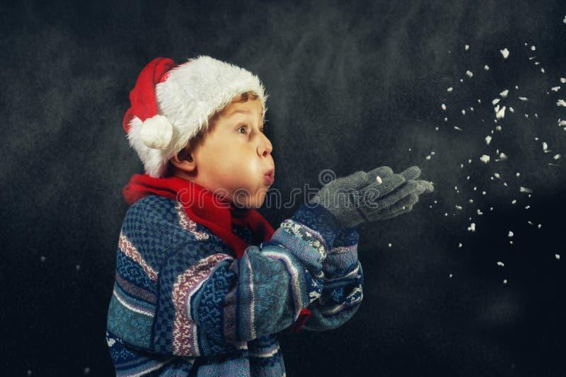 Porträt eines Jungen im Winter, des Kindes in einem Sankt-Hut und der warmen Strickjacke lizenzfreies stockbild