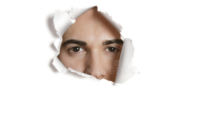 Porträt eines jungen kaukasischen Mannes, der von zerrissenem Papierloch späht lizenzfreie stockfotografie