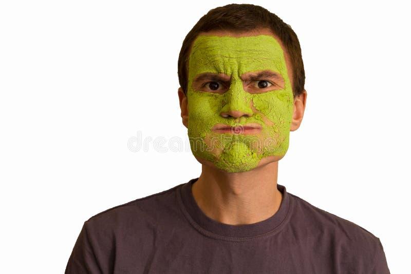 Porträt eines jungen Kerls mit einer grünen Gesichtsmaske stockfotografie