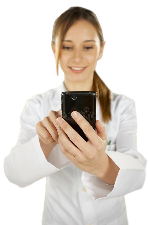 Porträt eines jungen lächelnden Doktors, der smartphone verwendet stockfotografie