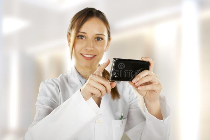 Porträt eines jungen lächelnden Doktors, der smartphone verwendet lizenzfreie stockfotografie