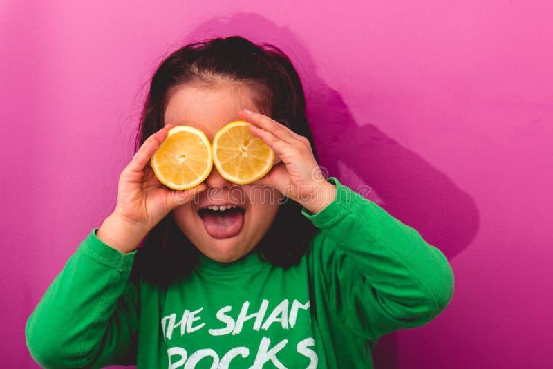 Porträt eines jungen Mädchens, das zwei hält, schnitt Zitronen in ihren Augen stockfotografie