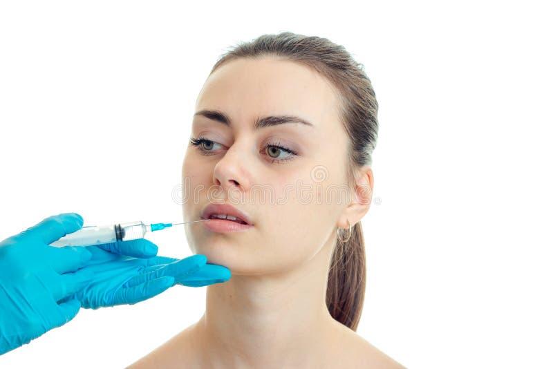 Porträt eines jungen Mädchens an einem Cosmetologist, den behandschuht ihren Stichel auf den Lippen macht stockbilder