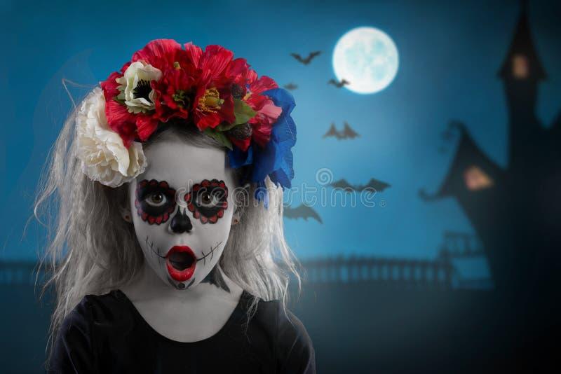 Porträt eines jungen Mädchens in einem Make-up auf einem Halloween-Kranz mit roten Blumen auf ihrem Kopf lizenzfreie stockfotografie