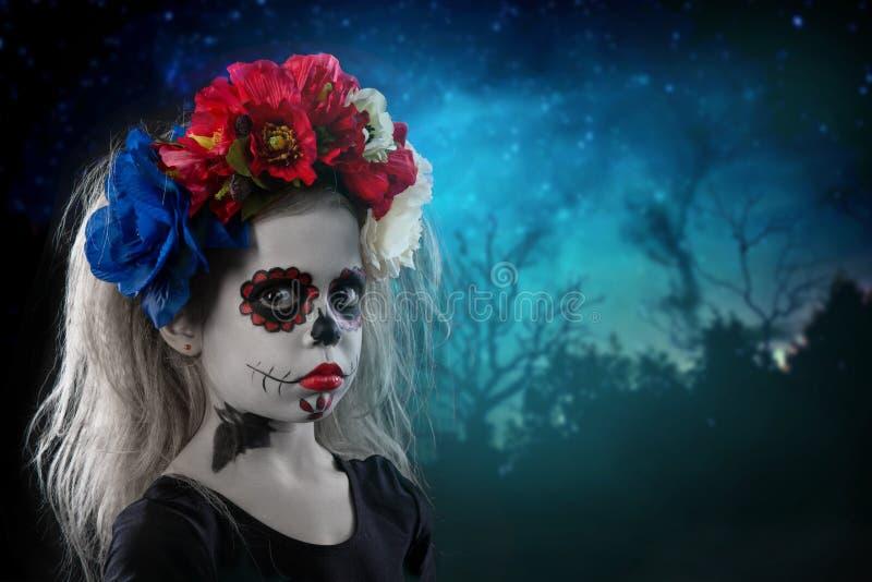 Porträt eines jungen Mädchens in einem Make-up auf einem Halloween-Kranz mit roten Blumen auf ihrem Kopf lizenzfreie stockfotos