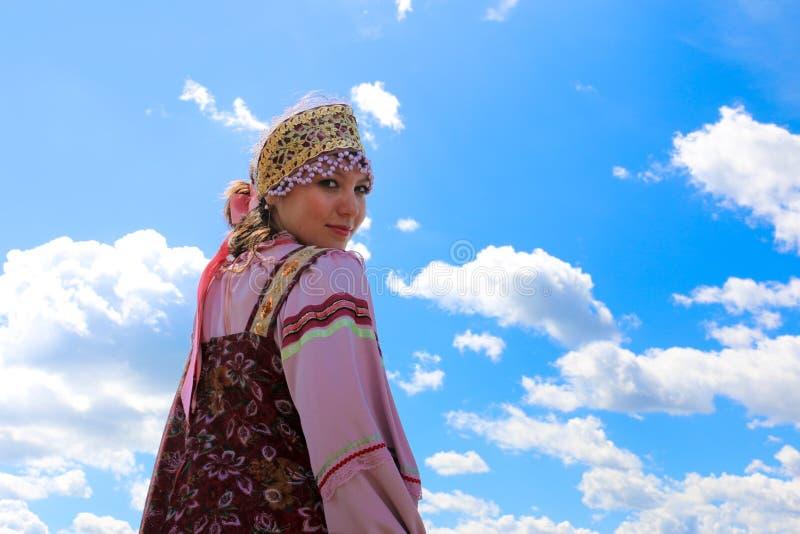 Porträt eines jungen Mädchens im russischen Volkskostüm auf dem Himmelhintergrund stockfotografie