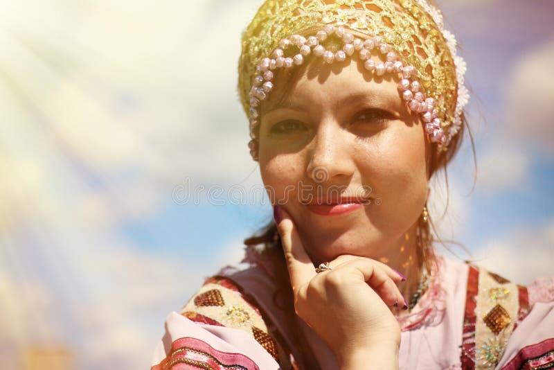 Porträt eines jungen Mädchens im russischen Volkskostüm auf dem Himmelhintergrund lizenzfreie stockfotografie