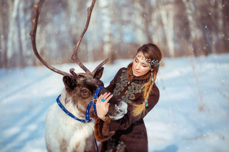 Porträt eines jungen Mädchens mit einem Ren im Winter lizenzfreie stockbilder