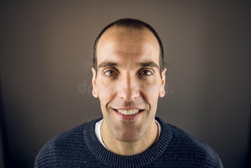 Porträt eines jungen Mannes, der die Kamera mit glücklichen Ausdruck und dem Lächeln betrachtet lizenzfreie stockfotos