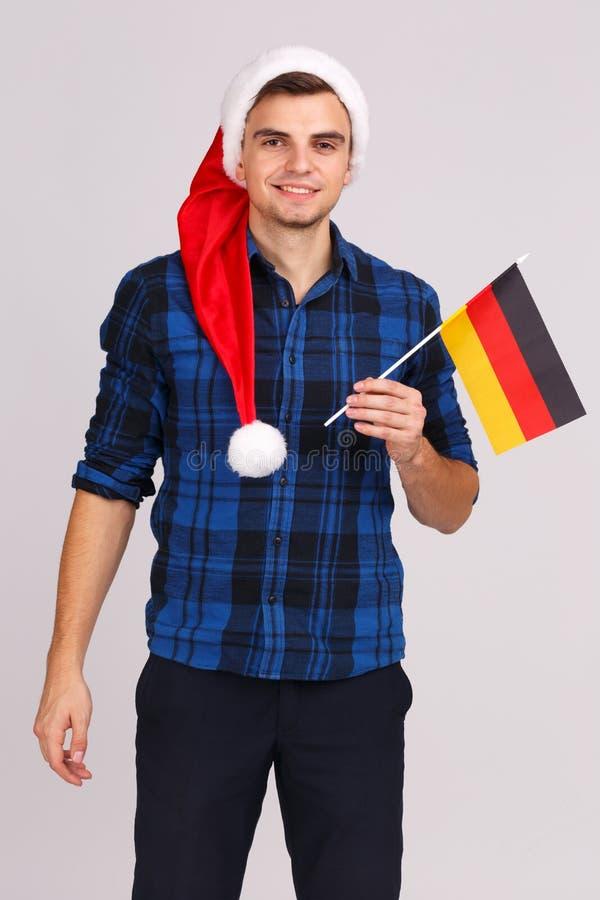 Porträt eines jungen Mannes in einem Sankt-Hut, mit der Flagge von Deutschland in seinen Händen stockbild