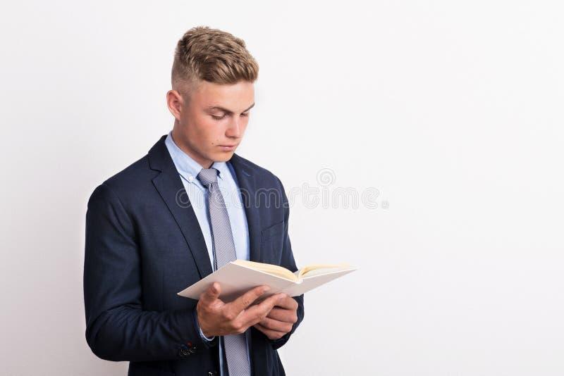 Porträt eines jungen Mannes in einem Studio, in einer Holding und in einer Lesung ein Buch lizenzfreie stockbilder
