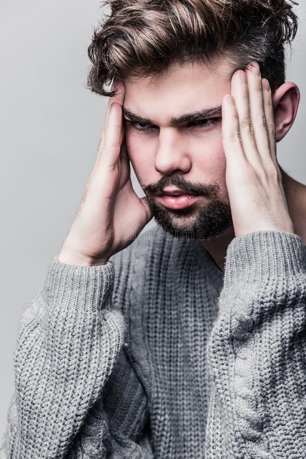 Porträt eines jungen Mannes im grauen Pullover Kopfschmerzen lizenzfreies stockbild