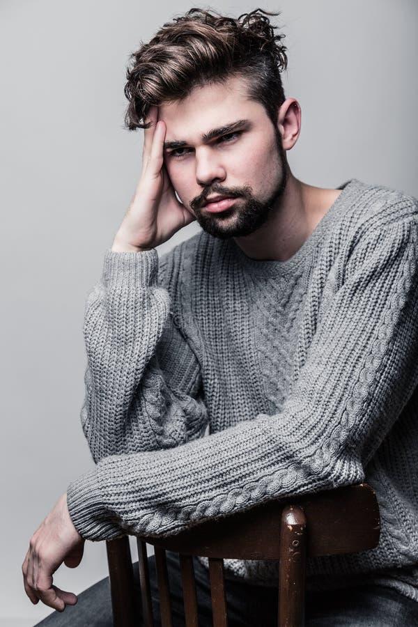 Porträt eines jungen Mannes im grauen Pullover Kopfschmerzen stockfotos
