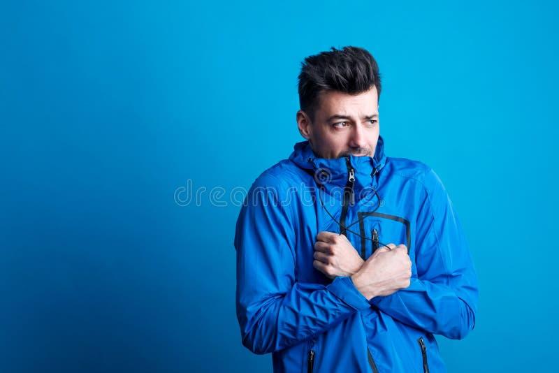 Porträt eines jungen Mannes mit blauem Anorak in einem Studio, glaubende Kälte Kopieren Sie Platz lizenzfreie stockfotografie