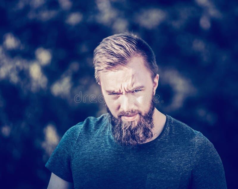 Porträt eines jungen Mannes mit einem Bart, der von der Sonne schielt, einen weichen natürlichen Hintergrund schaffend stockfotografie