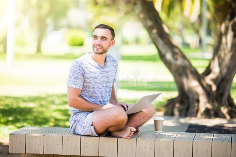 Porträt eines jungen Mannes mit Sitzen des Laptops im Freien auf Bank im Park stockbild
