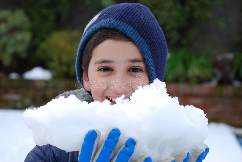 Porträt eines Jungen mit einem Schneeball stockbild
