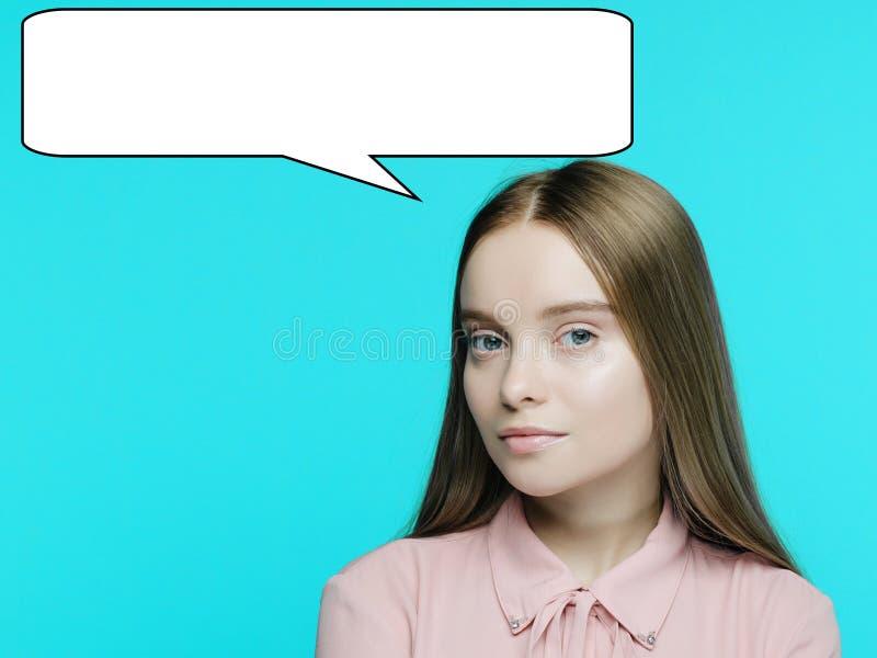 Porträt eines jungen nachdenklichen Mädchens mit einem Geplappergespräch über ihrem Kopf lizenzfreies stockbild