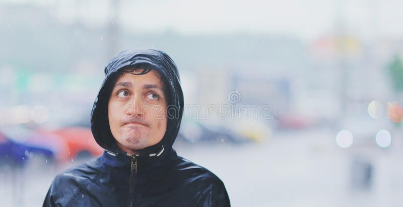 Porträt eines jungen nass Mannes in einer Jacke mit einer Haube im Regen auf unscharfer Hintergrundstadtstraße im Tsunami, Nahauf stockfoto