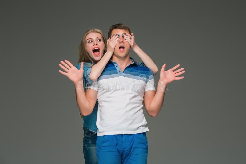 Porträt eines jungen Paares, das gegen grauen Hintergrund steht stockbilder